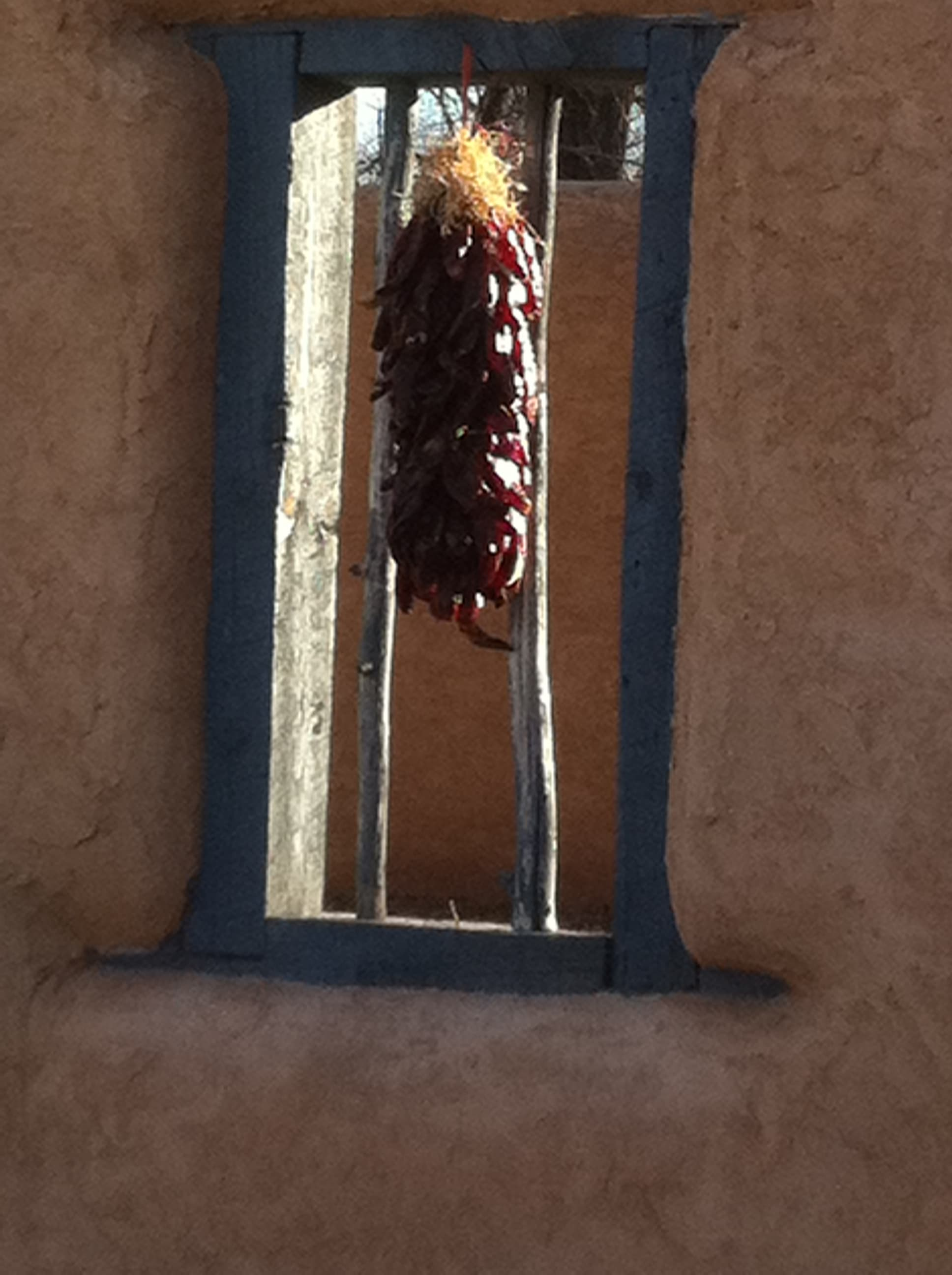 Chili ristra hanging in the window of an adobe wall in Albuquerque New Mexico.
