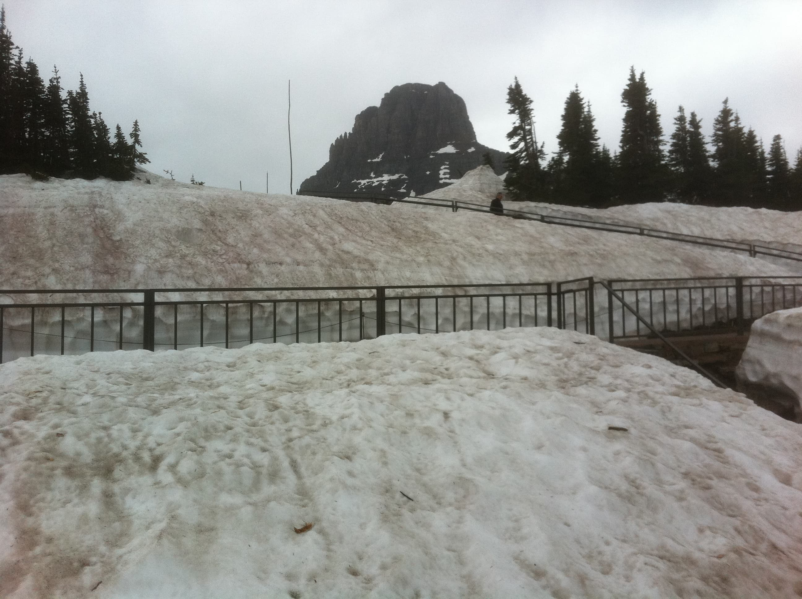 Snow surrounds walkway at Logan Pass Visitor's Center Glacier National Park in Montana.